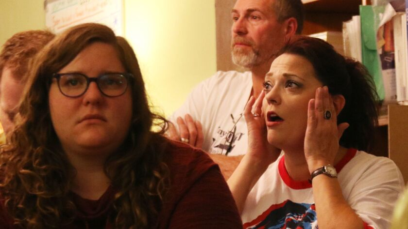 Debbie Santacroce, of West Bend, Wis., rubs the side of her head while watching election coverage at the Democratic Party of Washington County office on Nov. 8.