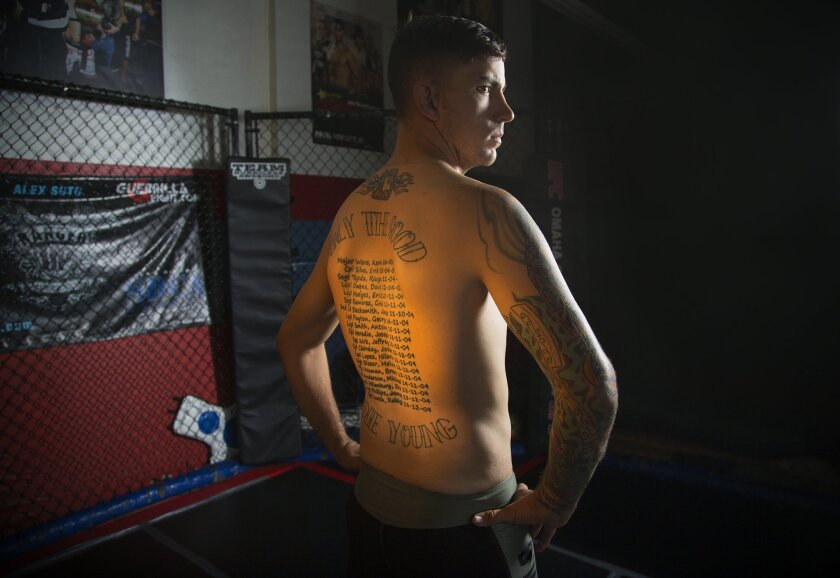 Shane Kruchten, an MMA fighter and Iraq veteran, proudly shows the tattoos on his back, a memorial to 19 fallen fellow Marines.