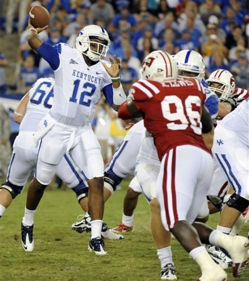 Quarterback Morgan Newton (12) of Kentucky drops back for a pass in front of defensive lineman Rammel Lewis (96) of Western Kentucky in the first quarter of an NCAA college football game on Thursday, Sept. 1, 2011, in Nashville, Tenn. (AP Photo/Frederick Breedon)