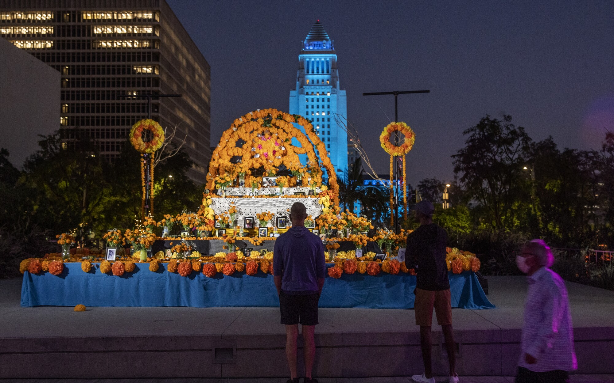 People stop before a community altar at downtown L.A.'s Grand Park.