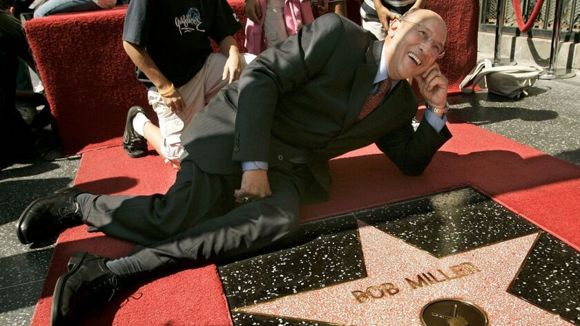 Hockey Hall of Fame announcer Bob Miller lies down next to his star on the Hollywood Walk of Fame on