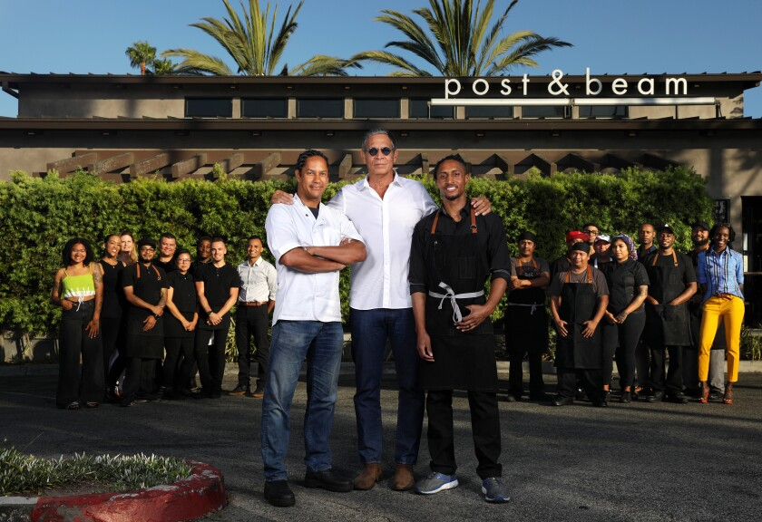 Restaurateur Brad Johnson, center, chef-owner John Cleveland, right, and chef-consultant Govind Armstrong, left, gather with the staff at Post & Beam restaurant in Baldwin Hills.