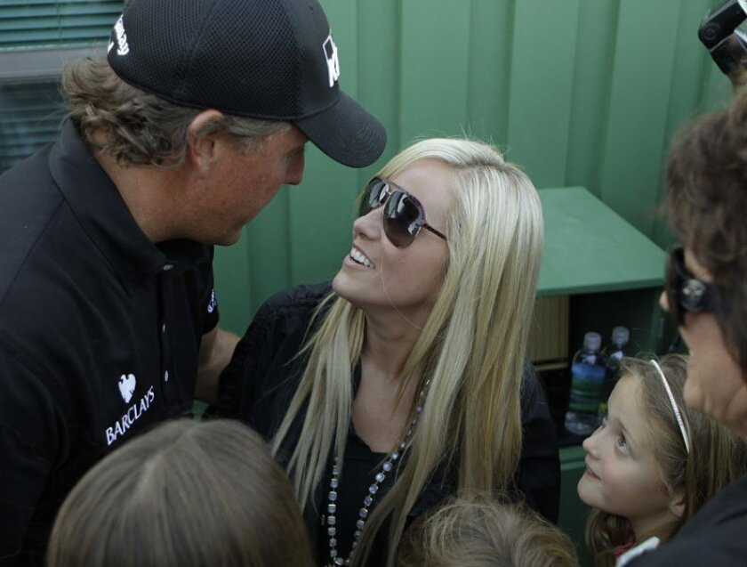 Phil Mickelson talks to his wife, Amy, as their daughter Amanda, right, looks on after Phil won his third Masters.