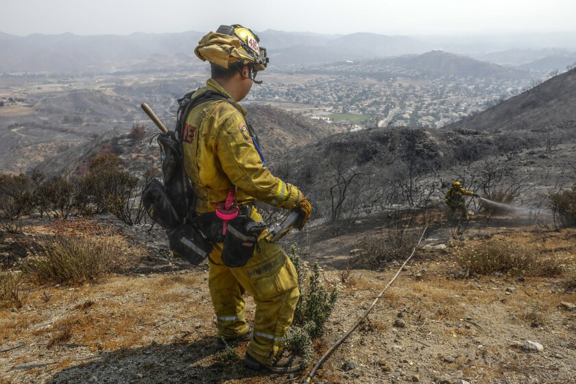 A firefighter douses hot spots in the McVicker Canyon neighborhood of Lake Elsinore.
