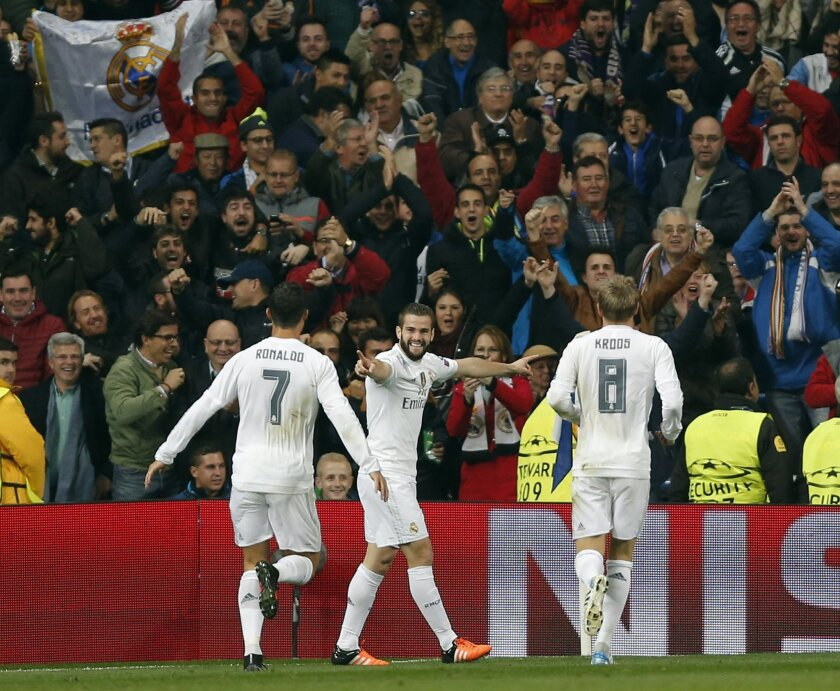 Real Madrid's Nacho Fernandez, center, reacts with Real Madrid's Cristiano Ronaldo, left, and Real Madrid's Toni Kroos after scoring the opening goal during their Group stage of Champion's League Group A soccer match against Real Madrid at the Santiago Bernabeu stadium in Madrid, Spain, Tuesday, No