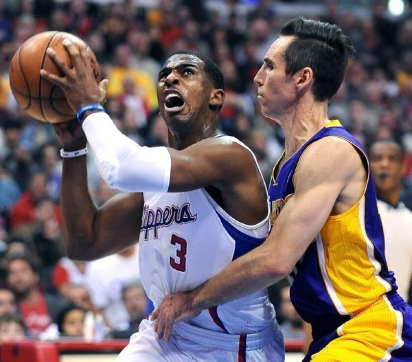 Clippers guard Chris Paul, left, drives to the basket on Lakers guard Steve Nash at Staples Center.