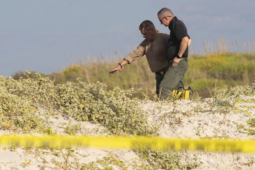 FILE - In this Oct. 28, 2019 file photo, several state agencies conduct an investigation on a Padre Island, Texas beach in Kleberg County after human remains were found. Investigators say two bodies found buried at the South Texas beach have been identified as a missing New Hampshire couple. The Kleberg County Sheriff's Office announced Friday, Nov. 1, that the deaths of 48-year-old James Butler and 46-year-old Michelle Butler are being investigated as homicides. (Courtney Sacco/Corpus Christi Caller-Times via AP, File)