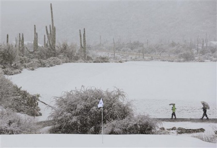Spectators make their way off the course during a snow storm during the Match Play Championship golf tournament, Wednesday, Feb. 20, 2013, in Marana, Ariz. Play was suspended for the day. (AP Photo/Ted S. Warren)