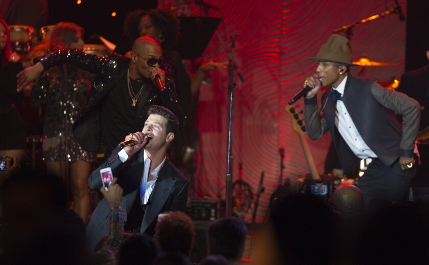 """T.I., from left, Robin Thicke and Pharrell Williams perform in Beverly Hills in January. Thicke and Williams are engaged with members of Marvin Gaye's family in a dispute over whether their 2013 hit """"Blurred Lines"""" infringed on Gaye's 1977 hit """"Got to Give It Up."""""""