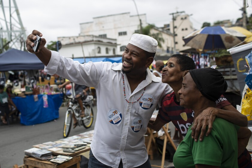 """Wagner Luiz Abreu Machado, a priest from the Afro-Brazilian faith Umbanda who goes by Waguinho Macumba, takes a selfie with residents as he campaigns for a seat on the Sao Goncalo City Council with the Brazilian Social Democracy Party (PSDB) in Sao Goncalo, Rio de Janeiro state, Brazil, Sunday, Nov. 8, 2020. """"No city councilor is committed to our causes,"""" Machado said, referring to the followers of African-influenced faiths. (AP Photo/Bruna Prado)"""