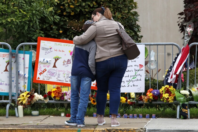 A mother and son visit a memorial at the Tree of Life synagogue in Pittsburgh on Sunday, the first anniversary of a shooting there that killed 11.