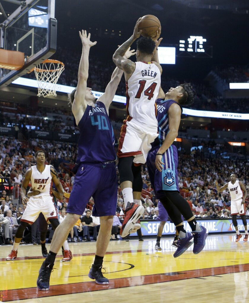Miami Heat guard Gerald Green (14) goes to the basket against Charlotte Hornets forward Cody Zeller (40) and Jeremy Lin (7) in the second half of an NBA basketball  game, Wednesday, Oct. 28, 2015, in Miami. The Heat won 104-94. (AP Photo/Alan Diaz)