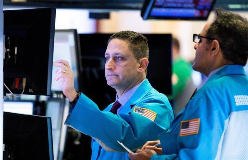 Varios trabajadores de la Bolsa contemplan los indicadores de mercado en una pantalla en Nueva York (Estados Unidos). EFE/Archivo