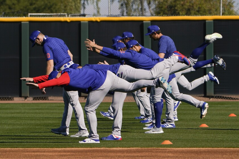 Chicago Cubs pitchers warm up during a spring training baseball workout in Mesa, Ariz., Monday, Feb. 22, 2021. (AP Photo/Jae C. Hong)