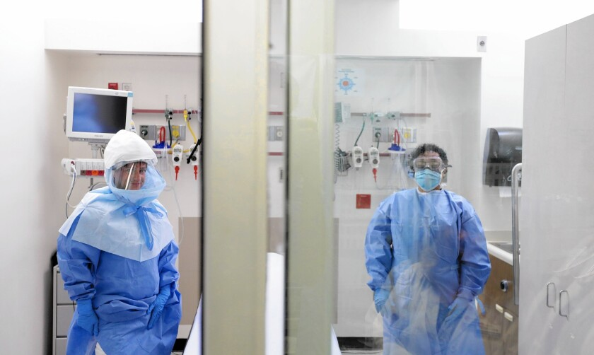 A medical worker wears a protective suit inside an isolation room appropriate to handle Ebola patients at Bellevue Hospital Center in New York.