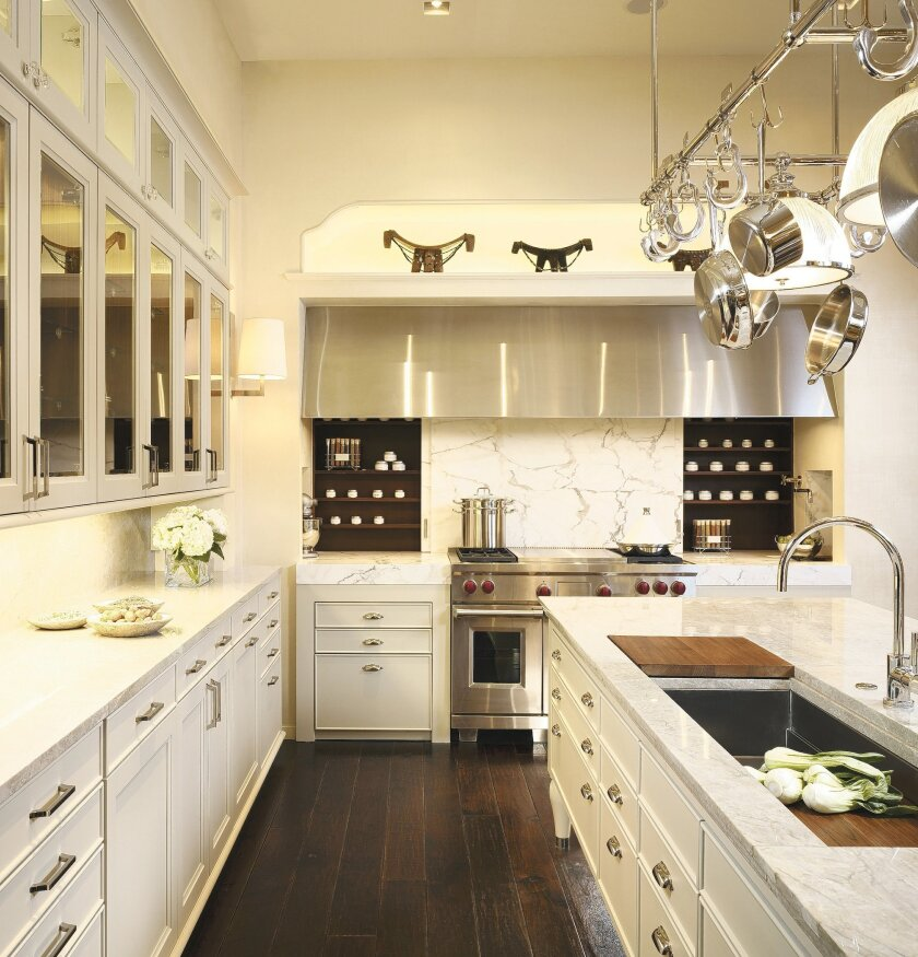 This mostly white kitchen gets contrast from dark wood flooring and textured marble countertops.