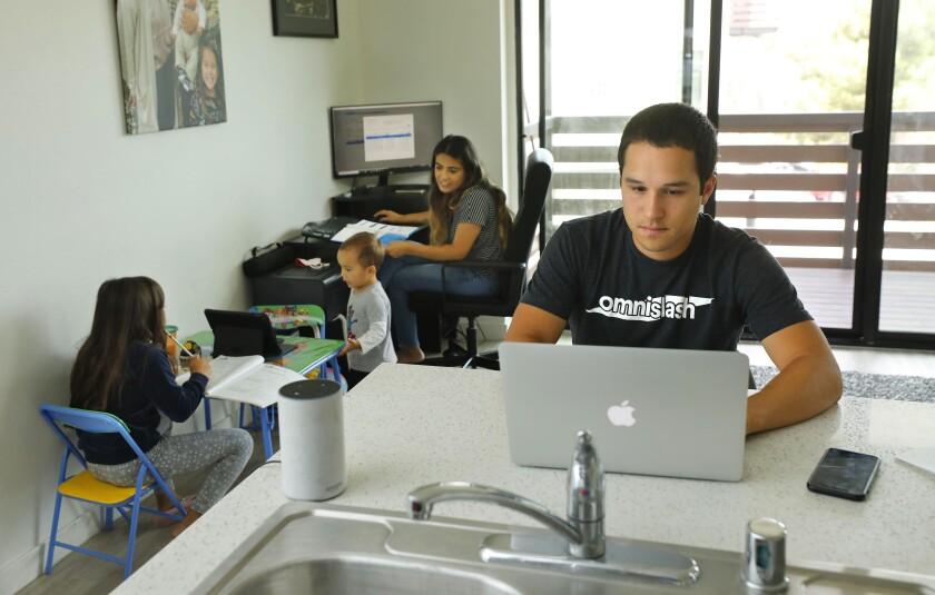 Lucas Fernandez, left, and his wife, Deicy, work from home while watching their children, Lucas Jr., 2, and Vienna, 7.