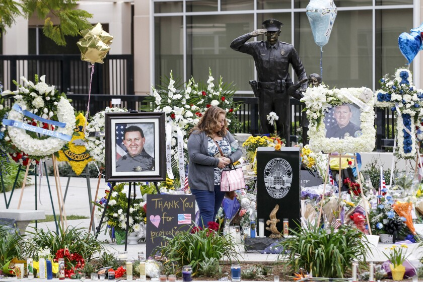 A woman visits a makeshift memorial for slain Whittier police Officer Keith Boyer to pay her respects.