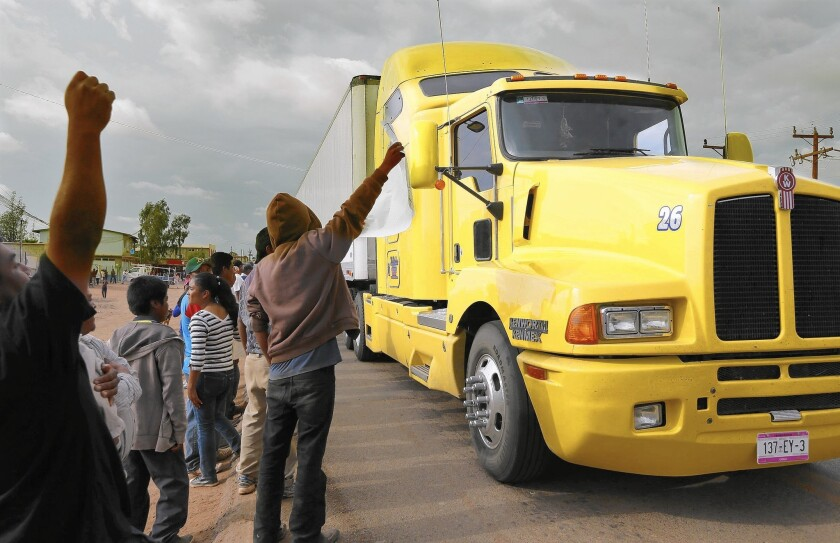 Farmworkers protesting low wages at Mexican export farms yell at a produce truck passing through Colonet.