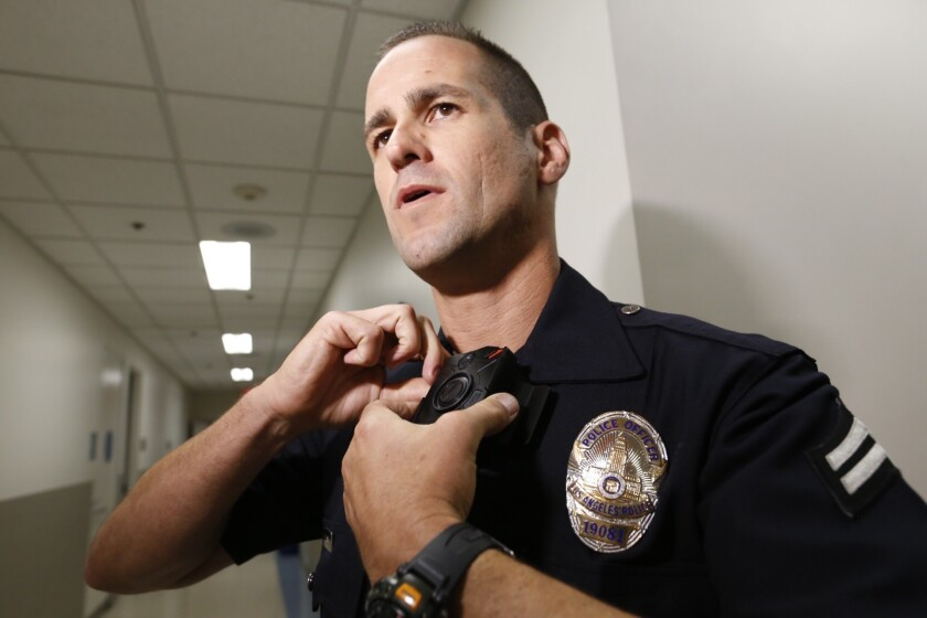 LAPD Officer Jim Stover demonstrates his new body camera at Mission Division headquarters in August.
