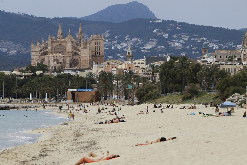 In this May 25, 2020 photo, people sit on the beach in Palma de Mallorca, Spain. Spain's Balearic Islands will allow for thousands of German tourists to fly in from June 15 for a two-week trial of tourism under new regulations against the spread of the new coronavirus. (Isaac Buj/Europa Press via AP)