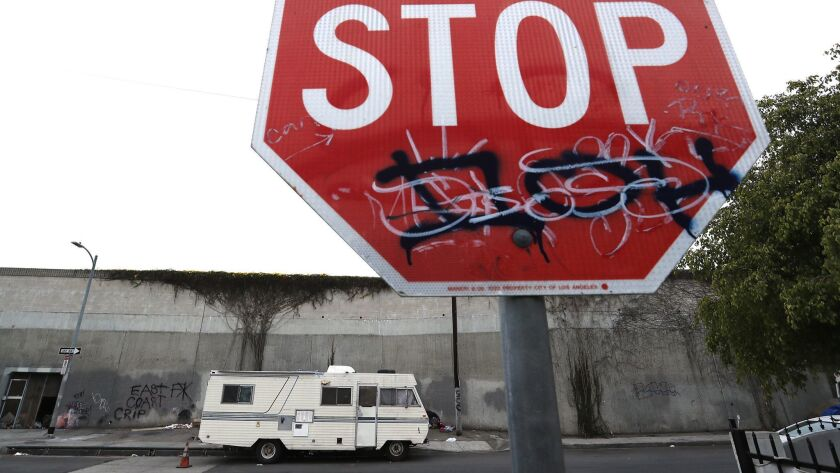 LOS ANGELES, CALIF. - MAY 22, 2018. A motorhome is parked on Grand Avenue beside a sound wall alon
