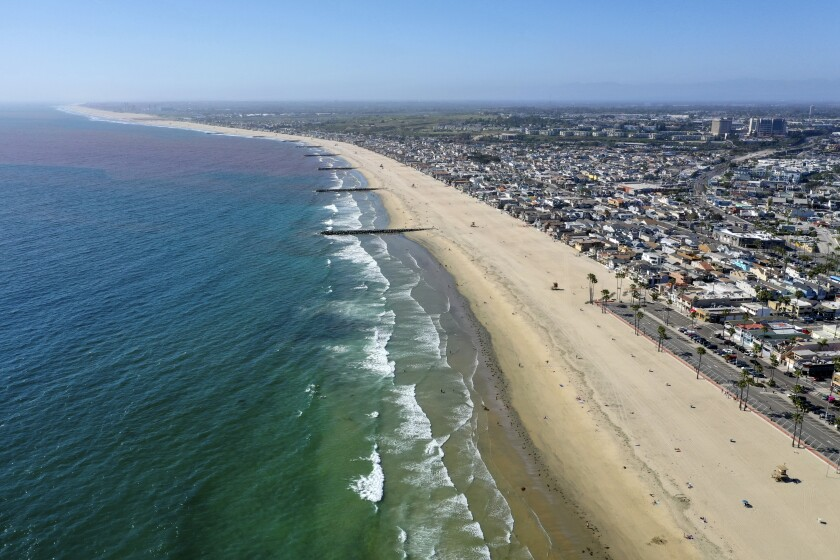 Beachgoers spread out across the sand in Newport Beach