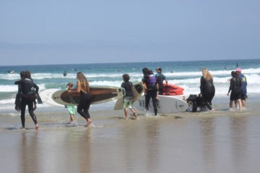 Dozens participate in the memorial paddle-out at La Jolla Shores beach for Caleb Acosta, with whom Ricochet surfed.