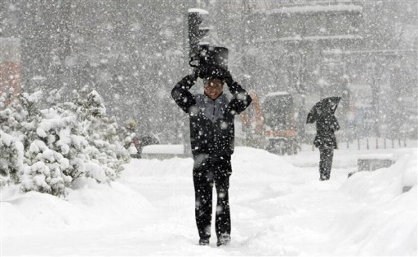 A South Korean man holds his bag to cover against heavy snow in Seoul, South Korea, Monday, Jan. 4, 2010. Thousands of workers in the South Korean capital are battling the city's heaviest snowfall in nine years. The snow has caused massive flight cancellations and seriously snarled road traffic. (AP Photo/ Lee Jin-man)