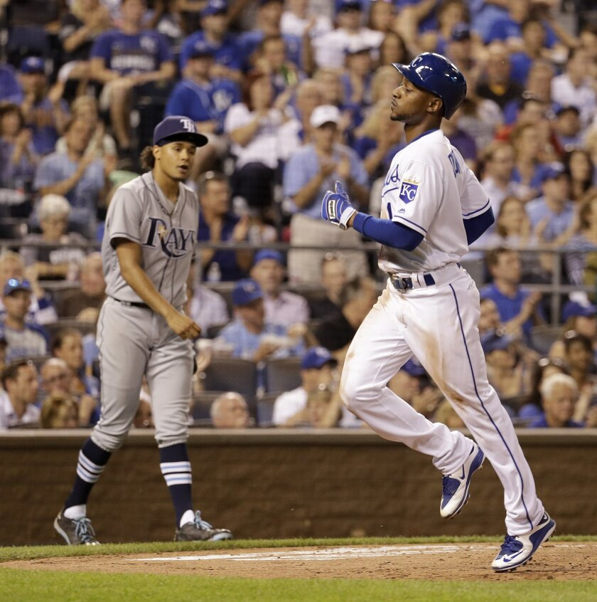 Kansas City Royals' Jarrod Dyson (1) crosses the plate past Tampa Bay Rays starting pitcher Chris Archer as he scores on sacrifice fly by Alcides Escobar during the sixth inning of a baseball game Wednesday, June 1, 2016, in Kansas City, Mo. (AP Photo/Charlie Riedel)