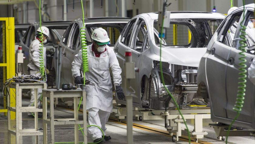 Workers at the assembly line of the recently opened Honda Motors factory in Celaya, Mexico.