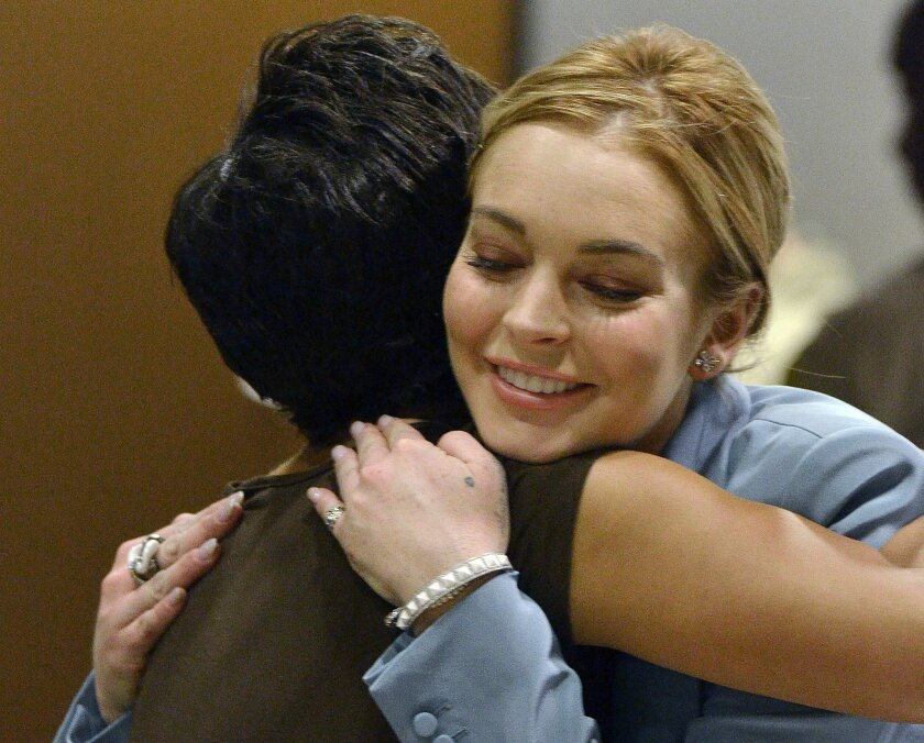 FILE - In a March 29, 2012 file photo, Lindsay Lohan, right, embraces her attorney, Shawn Chapman Holley after a progress report on her probation for theft charges at Los Angeles Superior Court. Few stars have become more closely associated with Los Angeles' court system than Lindsay Lohan, whose first arrest in May 2007 sparked a nearly eight-year court saga that finally ended Thursday, May 28, 2015. (AP Photo/Joe Klamar, Poo, File)