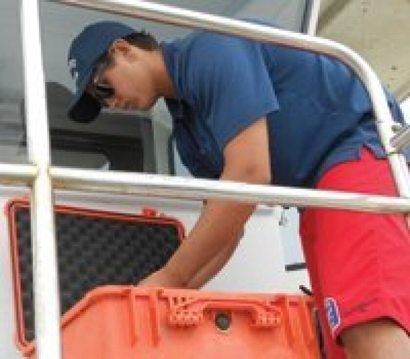 Lifeguard Cole Rogers organizes his equipment after coming to the aid of a stingray victim.