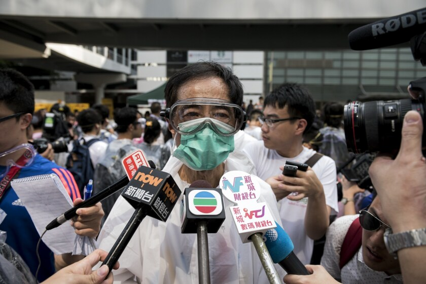 Pro-democracy activist and former legislator Martin Lee, wearing goggles and a mask to protect against pepper spray, talks to the media at a demonstration near the government headquarters in Hong Kong on Sept. 28.