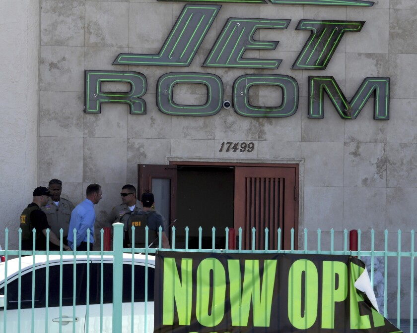 San Bernardino County Sheriff's deputies and FBI investigators lead a handcuffed man into the Jet Ro