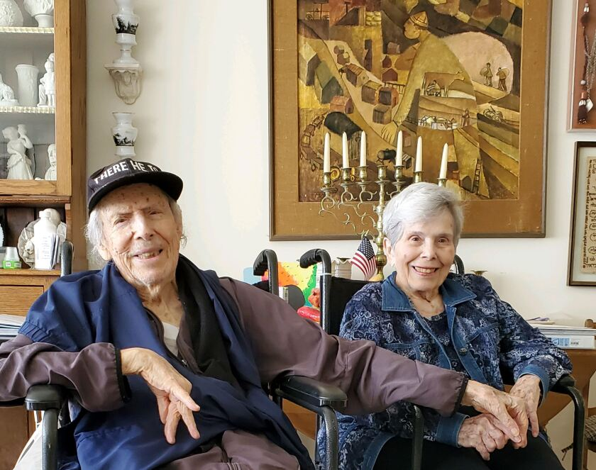 Norman and Sivia Mann smile as they sit side-by-side in wheelchairs at home