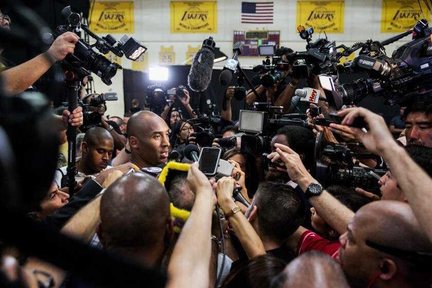 Lakers guard Kobe Bryant fields questions from reporters surrounding him during the Lakers' media day in El Segundo.