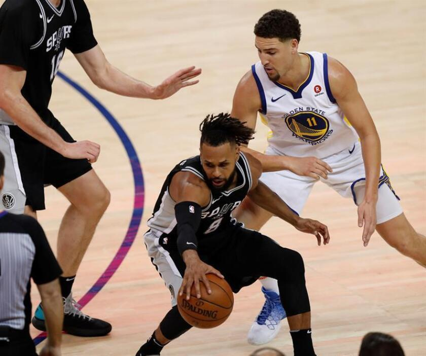 San Antonio Spurs guard Patty Mills (C) reaches for a loose ball against Golden State Warriors guard Klay Thompson (R) during the first half of the Western Conference first round Playoffs at Oracle Arena in Oakland, California. EFE