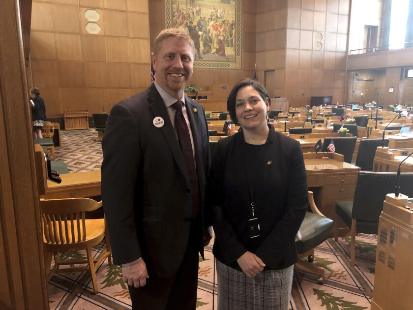 Oregon lawmakers Daniel Bonham, left, and Anna Williams pose for a photo on the floor of the Oregon House of Representatives on Thursday, Feb. 6, 2020 in Salem. Bonham, a Republican, and Williams, a Democrat, came together to sponsor a bill that would prevent a jail shared by four Oregon counties from renewing a contract with the US Immigration and Customs Enforcement to hold immigrants that ICE has detained. The lawmakers have different motives but came together to craft the legislation even as the Oregon Legislature is deeply divided, with minority Republicans threatening a walkout over a climate change bill. (AP Photo/Andrew Selsky)