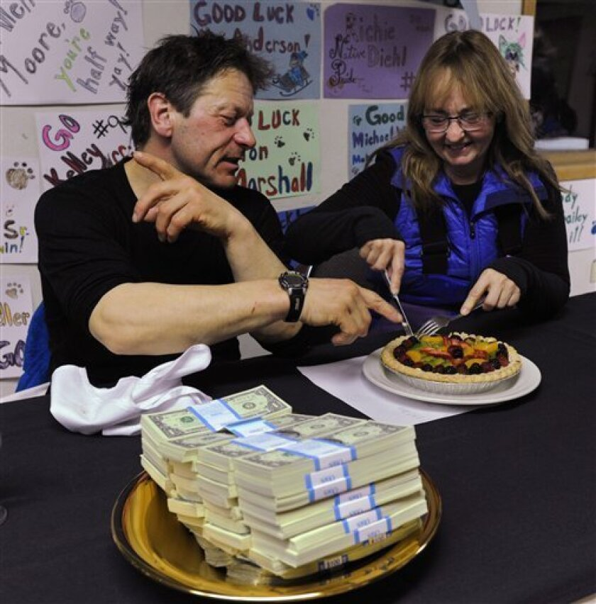Four-time Iditarod champion Martin Buser and his wife, Kathy Chapoton, eat a special meal prepared for the First to the Yukon award winner in Anvik, Alaska, during the Iditarod Trail Sled Dog Race, early Friday, March 8, 2013. Besides the meal, there are two more gifts for the first musher: $3,500,