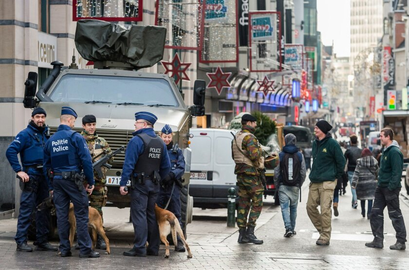 Belgian Army soldiers and Belgian police patrol a shopping street in the center of Brussels on Wednesday, Nov. 25, 2015. Students in Brussels have begun returning to class after a two-day shutdown over fears that a series of simultaneous attacks could be launched around the Belgian capital. Underground transport in Brussels is also slowly starting up again after a four-day closure. (AP Photo/Geert Vanden Wijngaert)