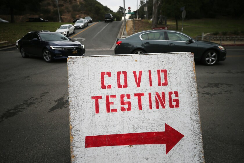 Vehicles line up to enter a COVID-19 testing site at Dodger Stadium.