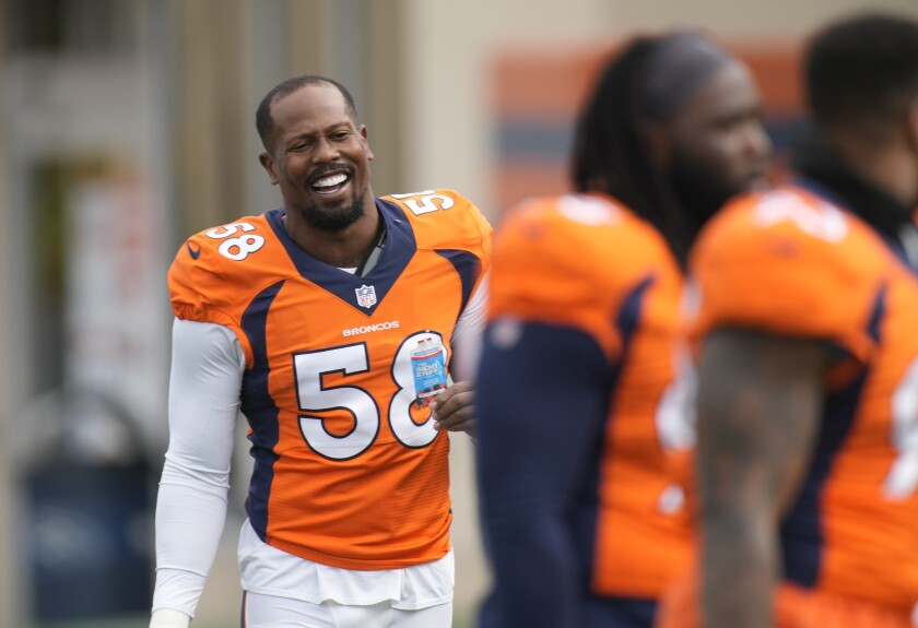 Denver Broncos outside linebacker Von Miller, left, jokes with teammates as they take part in drills at an NFL football training camp Tuesday, Aug. 3, 2021, at team headquarters in Englewood, Colo. (AP Photo/David Zalubowski)