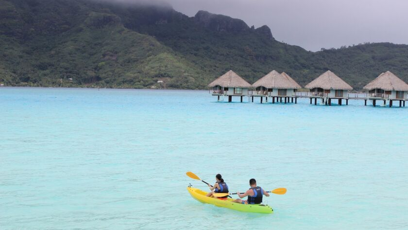 In this Nov. 4, 2015 photo, kayakers head out on the water from Le Meridien resort in Bora Bora. Bor