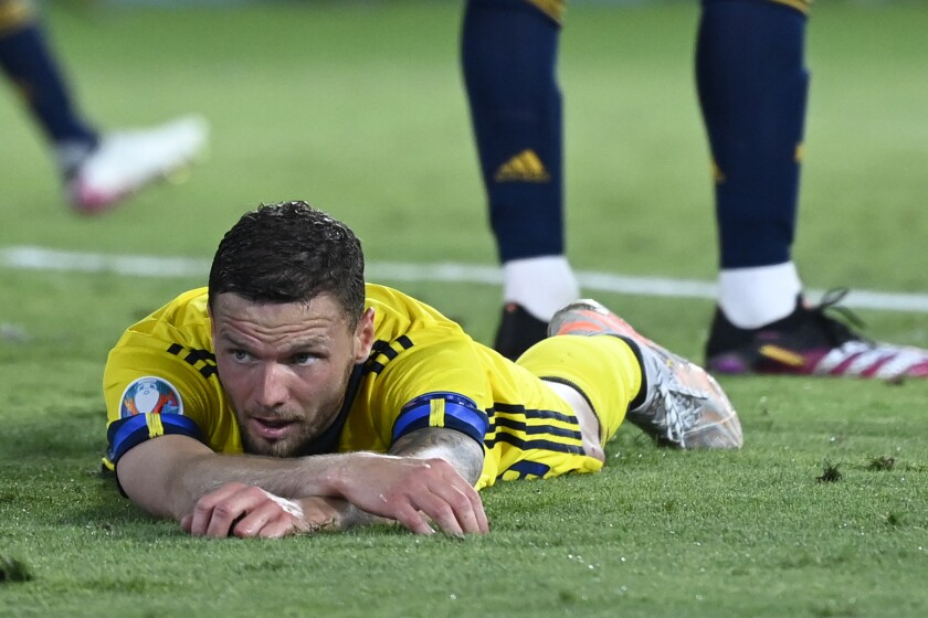 Sweden's Marcus Berg lies on the pitch during the Euro 2020 soccer championship group E match between Spain and Sweden at La Cartuja stadium in Seville, Monday, June 14, 2021. (AP Photo/Pierre Philippe Marcou, Pool)