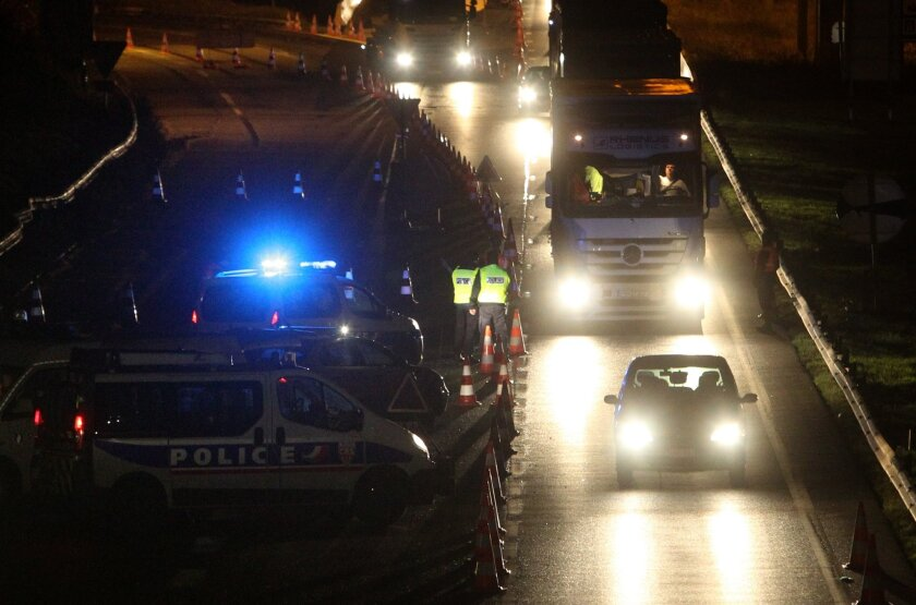 French police officers check vehicles on Tuesday at the border crossing to Belgium in Neuville-en-Ferrain as part of the hunt for fugitives wanted in connection with the Paris attacks.