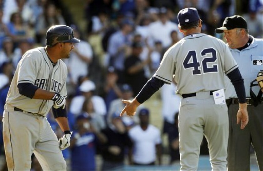 San Diego Padres' Jesus Guzman, left, and manager Bud Black talk with umpire Dale Scott after Guzman hit into a controversial triple play by the Los Angeles Dodgers in the ninth inning of a baseball game in Los Angeles Sunday, April 15, 2012. The triple play stood and Black was ejected. The Dodgers