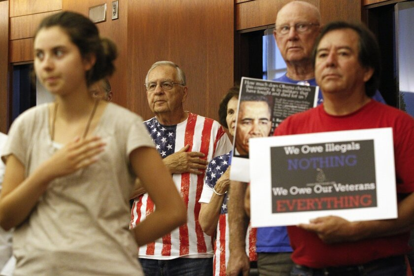 Those against the shelter for immigrant children, back and at right, hold their hands over their hearts during the Pledge of Allegiance before the start of the Escondido Planning Commission meeting.