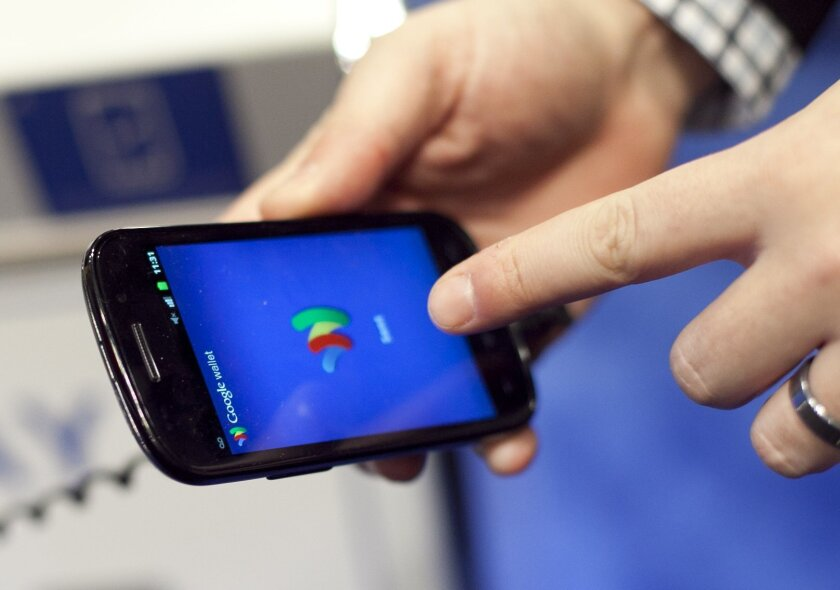 FILE - In this Jan. 17, 2012 file photo, a person tries a smartphone loaded with Google Wallet at the National Retail Federation in New York. Google is teaming up with three major U.S. wireless carriers in an effort to prod more people into using its mobile wallet and undercut the rapid success of Apple's rival payment service. (AP Photo/Mark Lennihan, File)