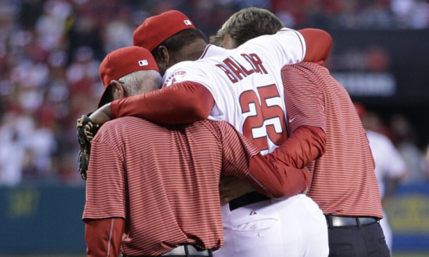 Angels hitting coach Don Baylor is helped off the field after breaking his leg while trying to catch a ceremonial first pitch during the team's season opener.